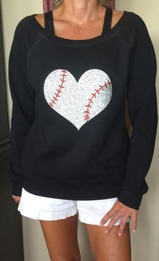 Shop now..What a way to show off your love of the game!  This off-the-shoulder top boasts a glittery heart-shaped baseball, perfect for layering your look at the next game.  Available in a variety of colors that will make the design POP! Sizing tends to run small, we suggest ordering a size up. 6.5 ounce 60% combed and ring spun cotton/40% polyester Off the shoulder fleece 1x1 rib neck line Wide ribbed cuffs and waistband Pre-laundered sponge fleece Side seamed Relaxed fit *PLEASE WASH RIGHT…