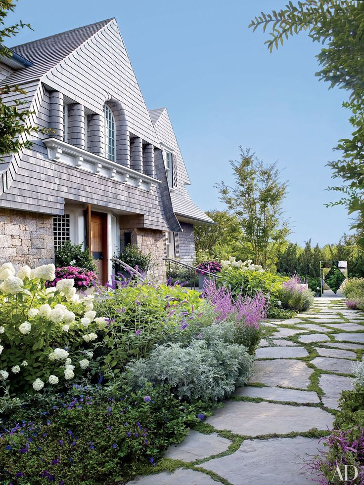 For the exterior of this Hamptons beach house, architecture studio Ike Kligerman Barkley employed a variety of traditional Shingle Style touches, such as fieldstone chimneys, fanciful variations in shingle pattern, and rounded pilasters.