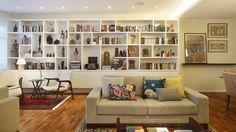 Uma estante grande organiza tudo: livros, objetos decorativos, artesanato, lembranças de viagem.  Fotografia: MCA Estudio.