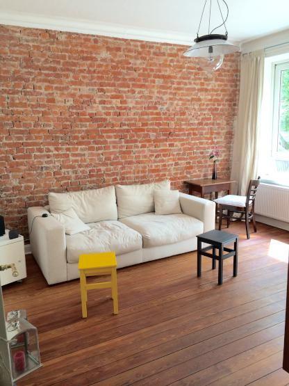 Schlichte Wohnzimmereinrichtung In Hamburg Weisse Couch Gelber Und Schwarzer Hocker Sowie Schne Ziegelwand Im