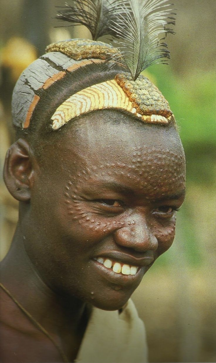 Africa | Bumi men scar their faces and wear multicoloured decorations made from clay which are often adorned with feathers | by Karl Gornin.