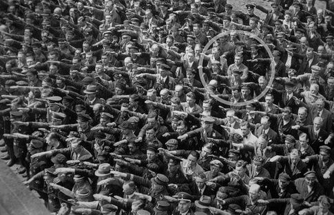 The man circled here is the only person in the gathering who has not raised this arm to make the honorary salutation. His name is August Landmesser .