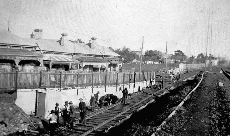 Men laying the Williamstown railway line. The line is in a cutting and there are houses in the background.