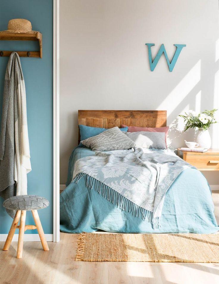 Dormitorio con pared gris piedra y azul, con cabecero y mesita de noche de madera, letra W decorativa, ropa de cama con estampado damasco, taburete y colgador