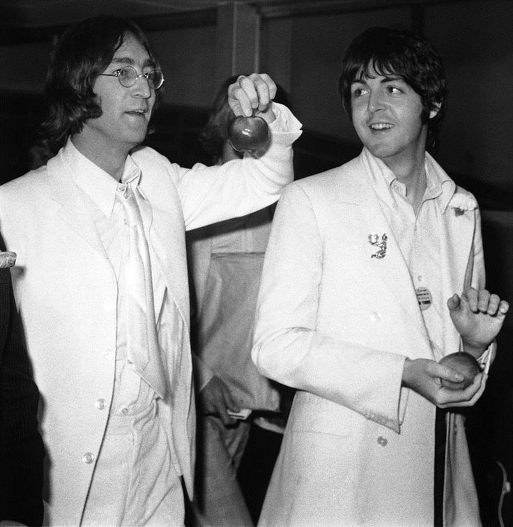 Beatles John Lennon and Paul McCartney at London Airport after a trip to America to promote their new company Apple Corps, 16th May 1968. They are both dressed all in white and carrying apples.