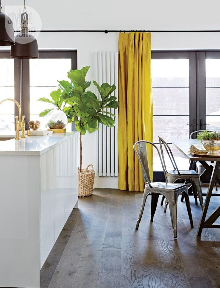 """Two sets of French doors, which replaced sliding ones, lead to the backyard deck. Yellow silk drapery adds a hit of colour to the neutral space. """"I didn't go for Roman blinds because I wanted something more dramatic,"""" says Stacy."""