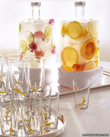 Vodka bottles encased in a frozen layer of colorful flowers and fruit.
