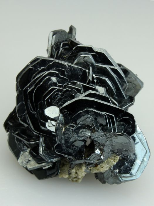 A super specimen of Hematite variety Iron Rose from the Riederalp area near Morel, Switzerland. This specimen is actually an excellent intergrown cluster of many Iron Roses. The Hematite crystals, measuring to 2cm across the major face, are thin hexagonal tabular crystals with beveled edges, up to 1mm thick. They have brilliant mirror metallic luster, and typical Hematite colour. A small amount of colourless-white Adularia can be seen at the base of the specimen.