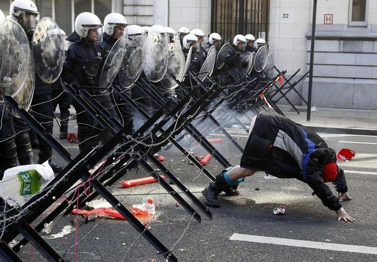 A demonstrator shows his bottom to riot police during a protest by European workers and trade union representatives to demand better job protection in the European Union countries in Brussels on March 24.
