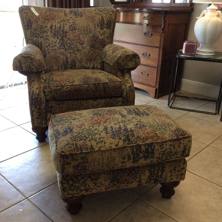 The LaZyboy chair has a matching ottoman. There are nailhead accents on the chair and both the chair and the ottoman have carved wooden legs.