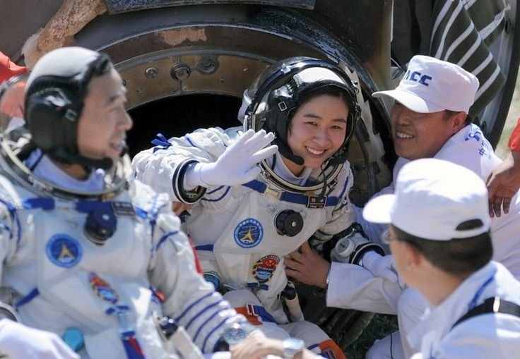 Liu Yang, China's first female astronaut, waves next to her comrade [Jing Haipeng] as she comes out of the re-entry capsule of China's Shenzhou 9 spacecraft.