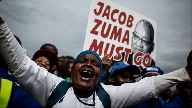 A Democratic Alliance (DA) party's supporters holds a placard reading 'Jacob Zuma must go' during a march against South African president Jacob Zuma on April 7, 2017 in Johannesburg.