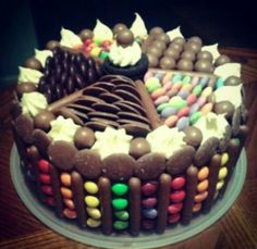 Double layered chocolate cake (oreo icing - butter icing with oreos in it - in the middle) with chocolate icing, decorated with chocolate fingers, m&ms, skittles, chocolate buttons, malteasers, smarties, minstrels, vanilla icing and an oreo.