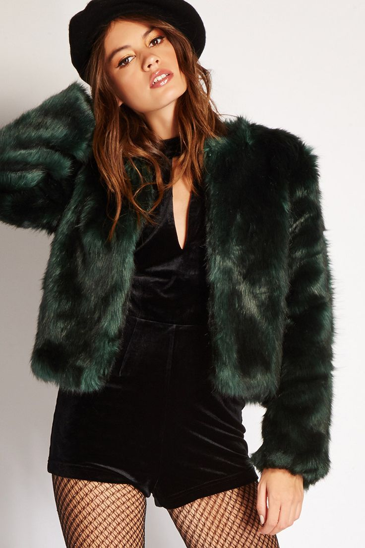 A collarless faux fur jacket with satin lining, a hook-eye closure at the neckline, and long sleeves.