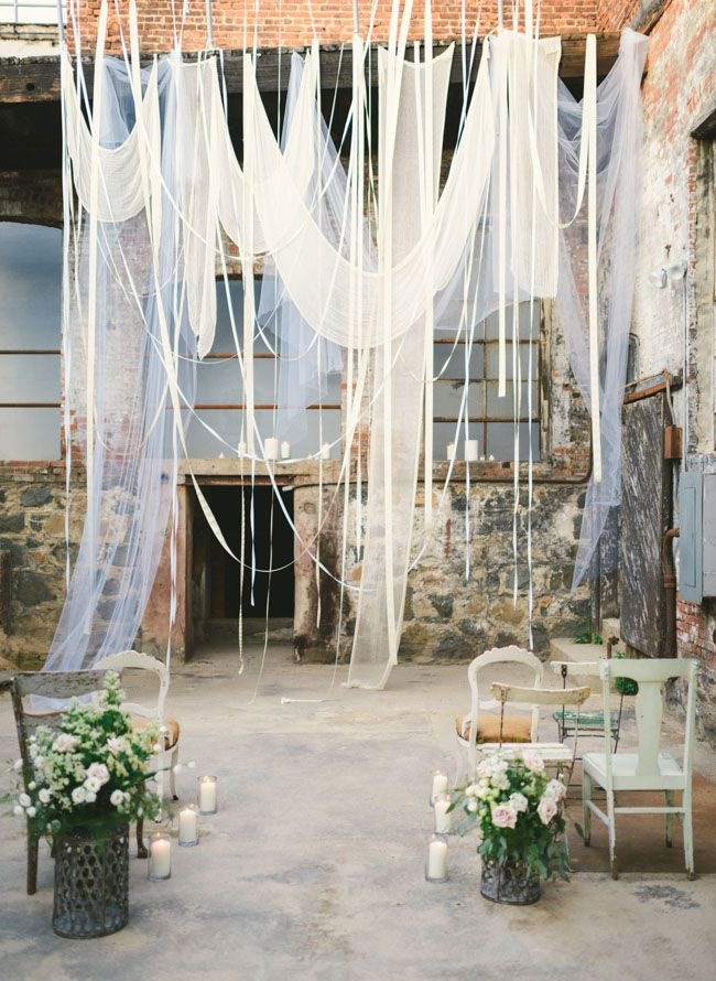 Lovely flowing fabric for a ceremony backdrop in an old warehouse  inexpensive tulle or old sheer curtains or old cute sheets could also be used