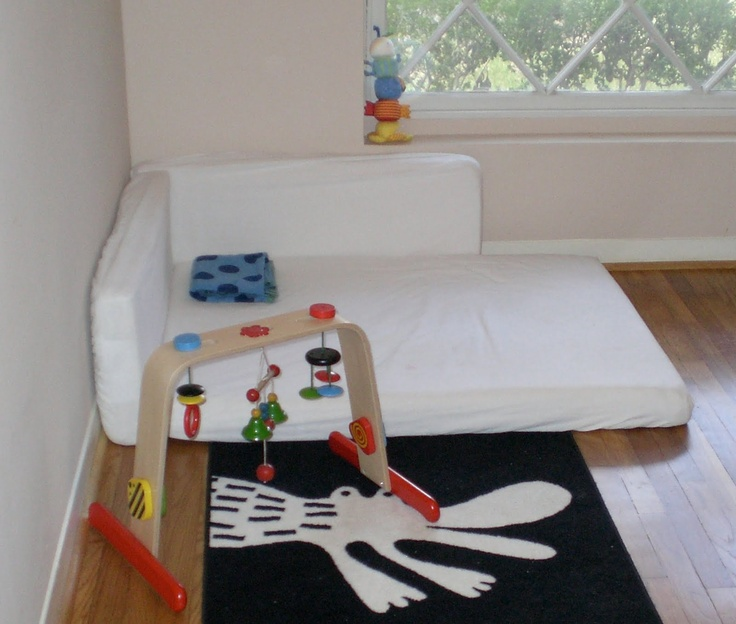 Montessori floor bed with wall bumpers. Play gym toys