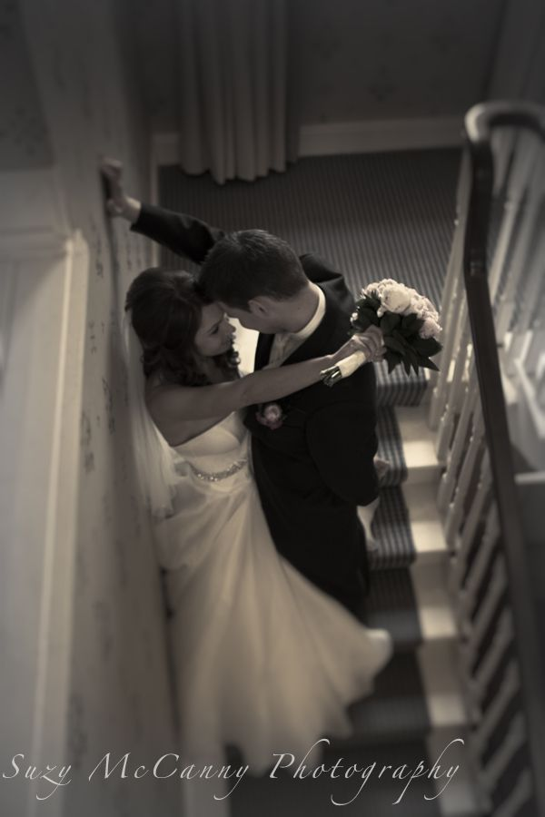 Black and white photo, romantic wedding photo of bride and groom on the stairs with flower bouquet
