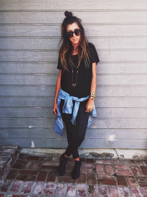 black leggings, oversized loose black tshirt, light blue denim collared button up shirt wrapped around the waist, long simple necklace, and black shoes.