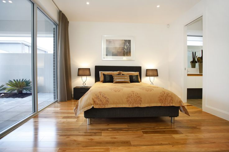 Stylish and sleek timber floorboards give this bedroom warmth, while the window wall allows natural light during the day...