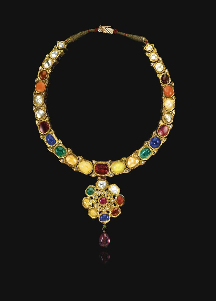 An enamelled and gem-set Navratna necklace, India, late 18th century comprising linked elements of octagonal form supporting a floral rosette pendant, each set with gemstones of varying colours, including white sapphires, pink coral, emeralds, rubies and diamonds, the reverse decorated with flowering plants and floral rosettes in white, green and red enamel, cabouchon ruby drop pendant 19cm. length