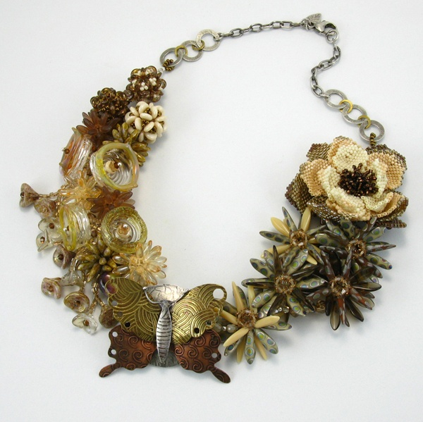 A statement necklace incorporating many bead styles, beadweaving, and metalsmithing. The butterfly and chain are handmade by the artist. $758.00 #statementjewelry #statementnecklace #jewelry #necklace #flowernecklace #beadweaving #fashion