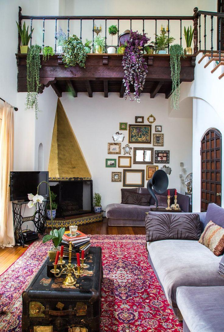 Salon bohème/boho avec tapis oriental/iranien, accumulation de plantes et cadres/miroirs au mur