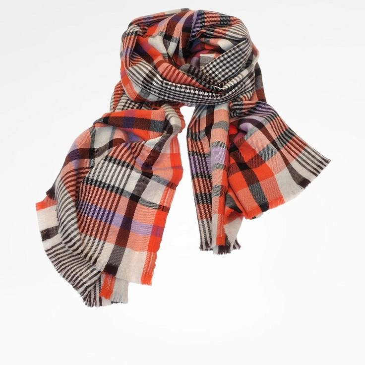 Loom scarf in pure wool. Mixed check print. Wide-cut with a wraparound design. Edges are not raw, but well defined. The coloring is based on shades of vermilion and lilac.
