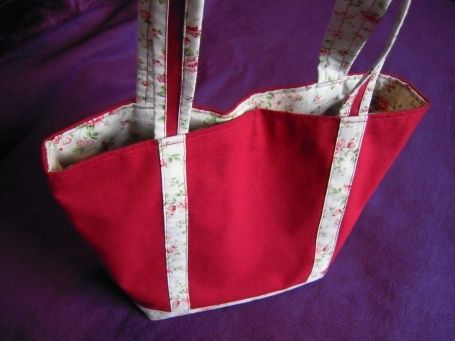 Sac Printemps Rouge Foncé Sac en toile/coton rouge foncé. Décoré de 3 bandes blanches à motifs floraux, en harmonie avec la doublure. Pratique, une poche intérieure permet de ranger son portable ou des accessoires, et sa fermeture magnétique sécurise...
