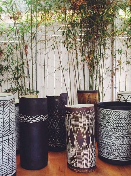 decorative pots with bamboo in them. U get privacy without the bamboo invading everything