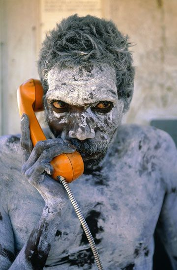 Aboriginal man using newly installed phone for the first time in Amhem Land, Australia, ca. 1975. Photo by Penny Tweedie [360x550].