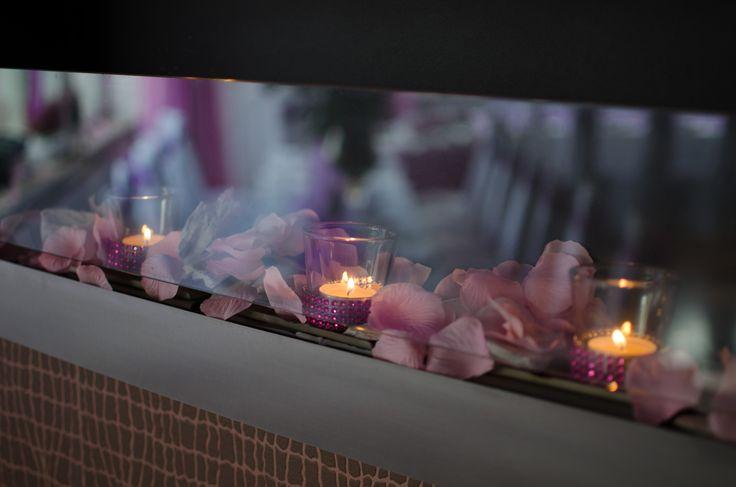 Świeczki wśród kwiatów w sali weselnej.