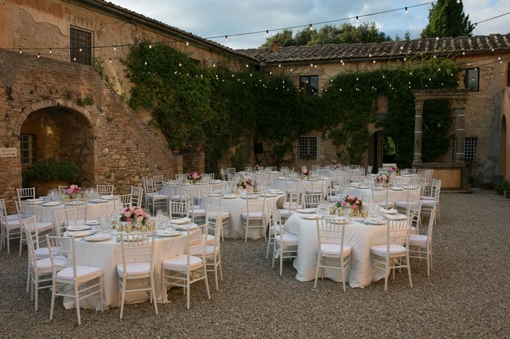 Private Italian courtyard decorated for wedding with round white cloth tables, topped with pink rose and gold centerpieces