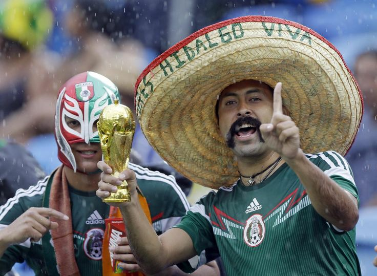 Mexican supporters gesure as they stand in the rain before the start of the group A World Cup soccer match between Mexico and Cameroon in the Arena das Dunas in Natal, Brazil, Friday, June 13, 2014