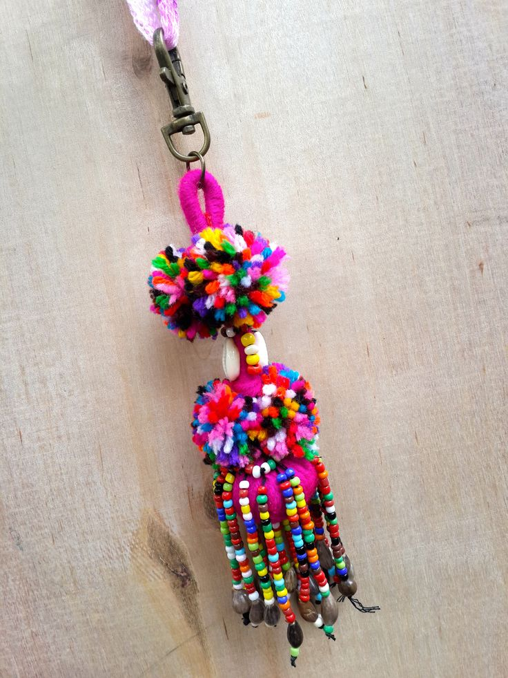 Colorful Pom Pom accessory with beaded fringe. It features two shells on each…