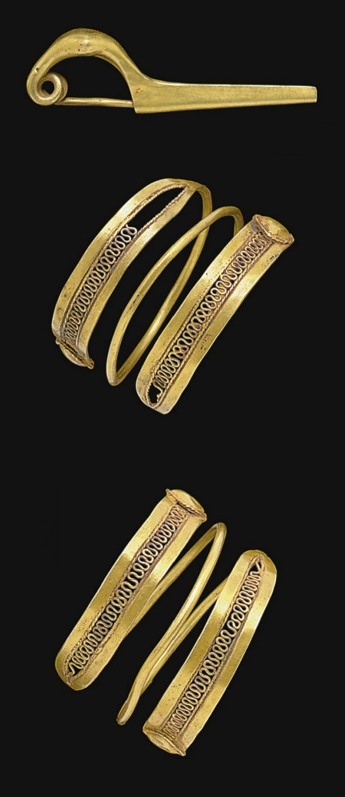 A PAIR OF ETRUSCAN GOLD HAIR COILS AND A FIBULA   CIRCA MID 7TH CENTURY B.C.   The hair coils each formed from a length of plain wire coiled into a spiral, each end split into two strips enclosing an undulating wire framed by twisted wire, terminating in triangular bosses framed by twisted wire; the fibula of sanguisuga form, with a hollow arched bow and long narrow catchplate, the pin coiled where it emerges from the bow  Fibula: 1 5/8 in. (4.1 cm.) long