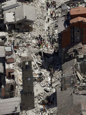 Residents and rescuers walk among the damaged buildings