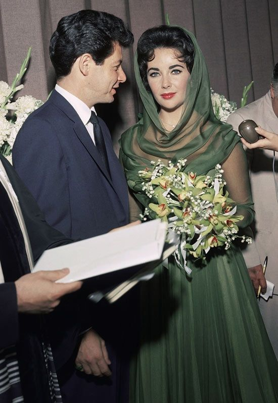 After the death of her third husband, Mike Todd, Elizabeth Taylor, famously ran to the arms of Mike's best friend Eddie Fisher for comfort. Eddie left his wife, Debbie Reynolds, Liz converted to Judaism, and they were married on May 12, 1959, at Temple Beth Shalom in Las Vegas. She wore a short forest-green silk dress featuring a hood and sheer sleeves and matching shoes. They divorced on March 6, 1964. Debbie Reynolds eventually forgave Liz and they became close friends until Liz died in…