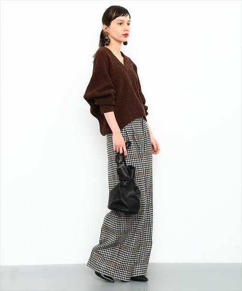 茶色のニットにグレンチェックのワイドパンツを合わせたポニーテールの女性