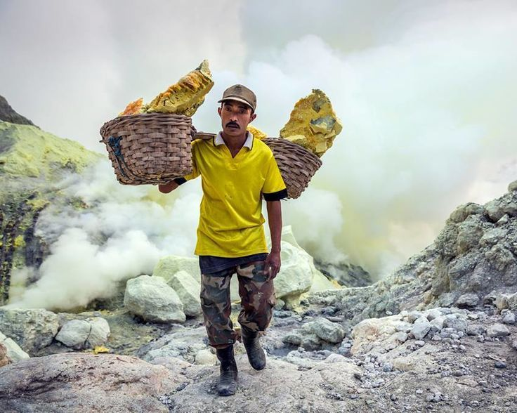 """""""80 Kilos"""" - this is a photo of one of the miners of Ijen Volcano in Indonesia. These guys mine and then carry on average 80 kilograms of sulfur up to the top of the volcano crater and then all the way to the bottom of the volcano only to head back up and do it again. This is one of the hardest jobs on the planet!   Photo by Ian Plant"""