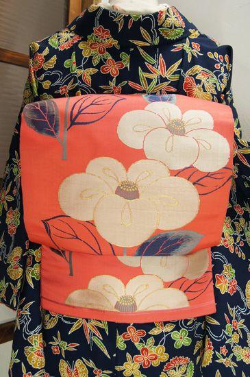 こっくりとしたピンク色の地に、ふっくら丸い花びらも愛らしい大輪の椿の花が織り出された大正ロマン・昭和レトロな情緒ただよう名古屋帯です。