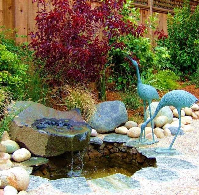 Jardin asiatique avec statue d'oiseau, pierres et petit étang