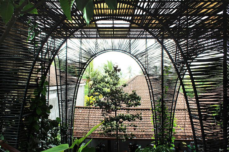 alexis dornier designs la pacha mama restaurant in bali..designed by alexis dornier, the restaurant's inner courtyard is covered with a canopy supported by bent steel tubes that rise above the existing building below. the vertical structural elements form a hybrid of a truss, a vault, and an arch, interwoven with rubber recycled from old truck tires. this structural framework provides space for plants and flowers to grow.