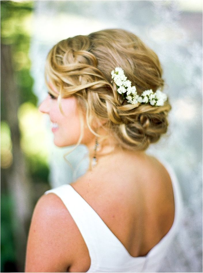 Loosely braided low wedding updo, with baby's breath and loose curls.   4th of July Wedding Inspiration Shoot | Bride Link