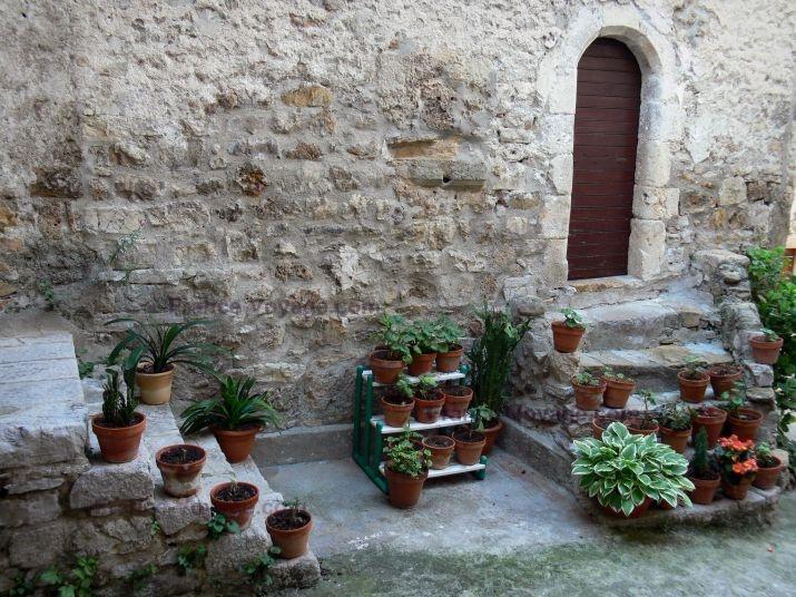 Saint-Guilhem-le-Désert : Gevel van een stenen huis, kleine trappen versierd met potten van planten