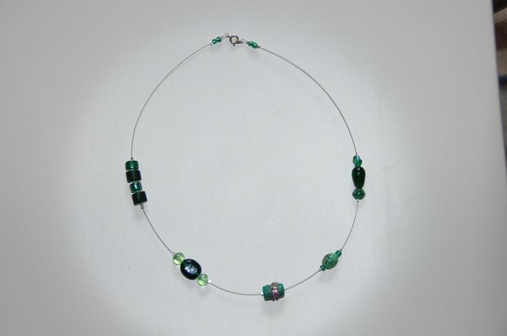 Collana con cavo di acciaio, perle di vetro verdi e perline metalliche argentate.