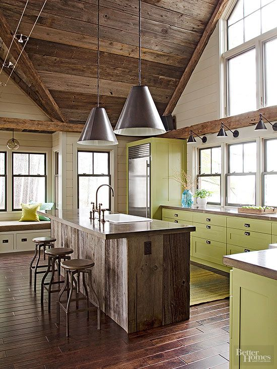 The contrast between ultra-modern cabinets and worn-in wood makes this one-of-a-kind kitchen work. The industrial-yet-rugged look is amplified with simple metal pendants, steel stools, and bright apple green paint on the cabinetry. The amount of natural light in this room prevents the dark wood from leaving the kitchen feeling like a cave. White paneled walls also help to create contrast between the darker wood on the ceiling and floors.