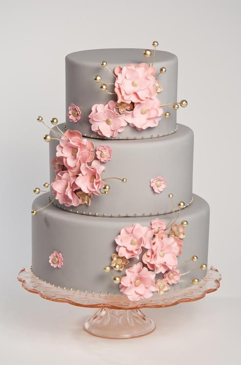 Pink blossoms and gold details pop against a sleek gray fondant- covered cake by sugar couture.