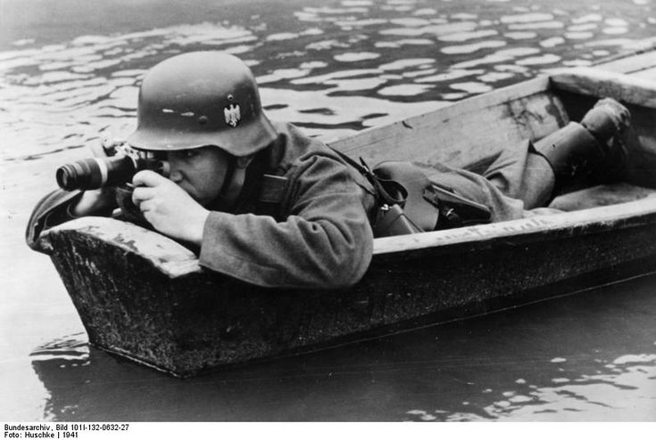 A photographer of a Propaganda Company at work on a river boat crossing somewhere in Poland, 1941. He is using a Leica camera with one of the early telephoto lenses.