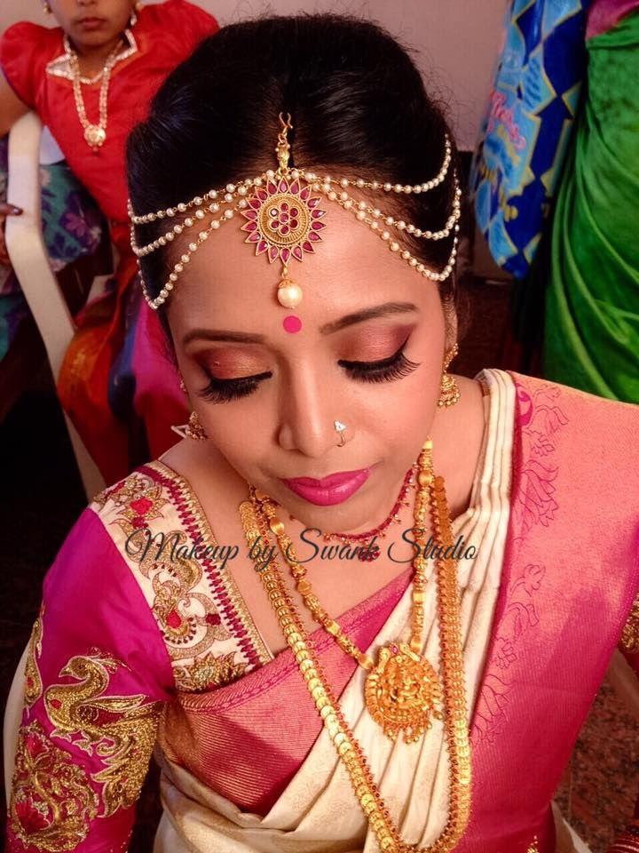 Traditional Southern Indian bride, Bhavya wears bridal silk saree and jewellery for her Muhuratam. Makeup and hairstyle by Swank Studio. Pink lips. Nose stud. Maang tikka. South Indian bride. Eye makeup. Bridal jewelry. Bridal hair. Silk sari. Bridal Saree Blouse Design. Indian Bridal Makeup. Indian Bride. Gold Jewellery. Statement Blouse. Tamil bride. Telugu bride. Kannada bride. Hindu bride. Malayalee bride. Find us at https://www.facebook.com/SwankStudioBangalore