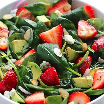 Create this light salad with avocado, strawberry, and spinach. Top with a poppy seed dressing for a perfect summer dish!
